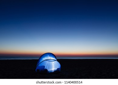 Lighted tent on the beach by the sea, daybreak