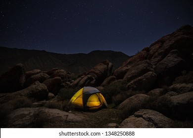 lighted up tent set up among rocks at night under a starry sky