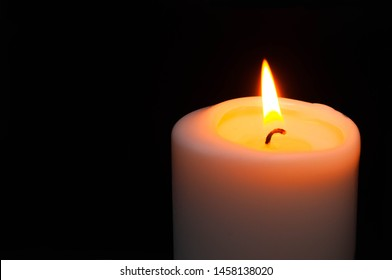 lighted wax white candle on black background