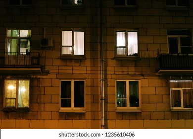 Lighted windows and balconies of an old night residential building
