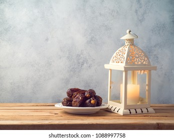 Lightened lantern and dates fruit on wooden table. Ramadan kareem holiday celebration concept