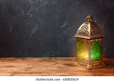 Lightened lantern on wooden table over dark background. Ramadan kareem holiday celebration concept
