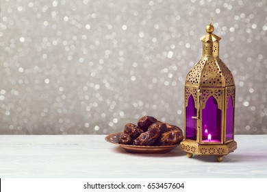 Lightened lantern on wooden table over bokeh background. Ramadan kareem holiday celebration concept