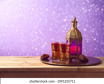 Lightened lantern, tea and dates fruit on wooden table. Ramadan kareem holiday celebration concept