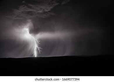 Lightening bolt striking the ground at night