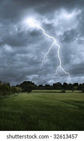 Lightening strikes from a stormy sky over a countryside landscape