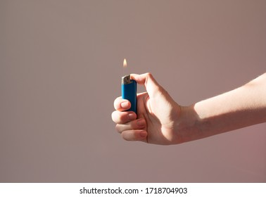 Lighter burns in the hand in the shade. A man holds a lighter with a flame. Fire and smoking concept - Shutterstock ID 1718704903