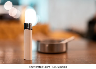 lighter in front of blurred cigarette and ashtray. cheap cigarette lighter. White cigarette lighter.  Lighter and silver ashtray with cigarette. Bokeh background. Wallpaper