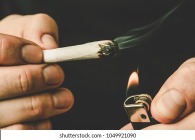 lighter and joint in his hands. A man smokes cannabis weed, a . Smoke on a black background. Concepts of medical marijuana use and legalization of the cannabis. On a black background