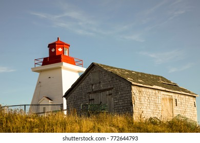 Lighthouse against blue skies in Cape Breton Highlands National Park, Nova Scotia, Canada.