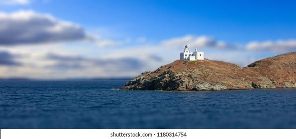 Lighthouse and agios Nikolaos church on rocky land. Kea,Tzia the sunny island, Greece. Blur cloudy sky background, banner.