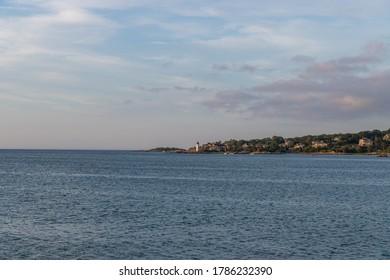 Lighthouse along the ocean horizon during sunset.