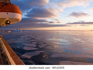 Lighthouse in the Arctic Sea at sunset. View from the boat