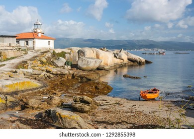 Lighthouse and beach on Punta Cabalo cape in Arousa island with a traditional dorna boat