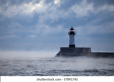 A lighthouse beacon shining in some rough weather.