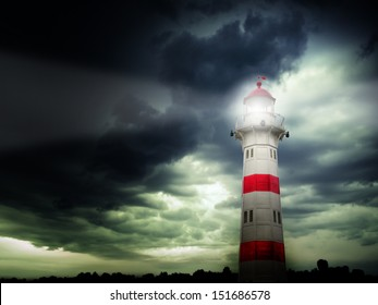 Lighthouse with beam against dark stormy sky