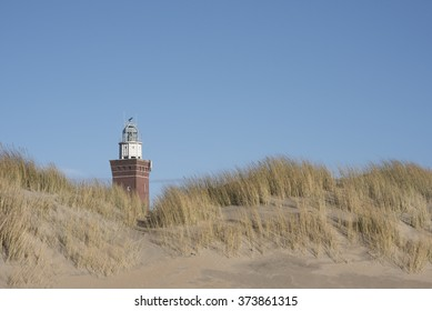 Lighthouse behind the dunes with a blue sky