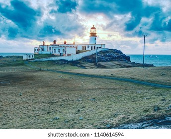Lighthouse building with tower against to evening sky. Popular Neist Point, spit of land Isle of Skye, Scotland