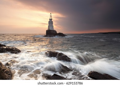 Lighthouse by the sea shore at sunrise