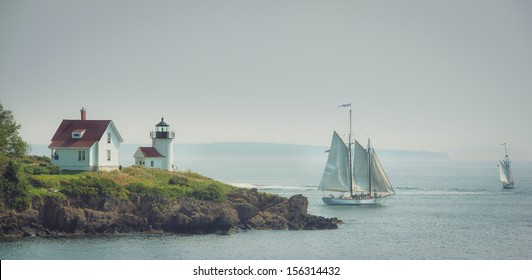 Lighthouse of Camden, Maine on Curtis island with schooner to the side