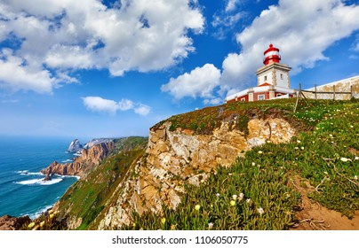 Lighthouse at Cape Roca (Cabo da Roca), most western point of Europe at coast of Atlantic Ocean in Portugal. Rocks at coastline and blue sky with clouds over skyline. Picturesque summer landscape.