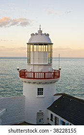 Lighthouse in the coast of Wicklow, Ireland. Sunset at the sea.