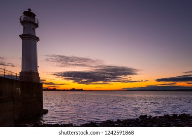 Lighthouse and colorful sunset with dramatic sky in Edinburgh, Scotland.