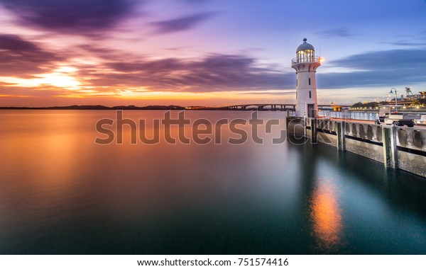Lighthouse during a colorful sunset over the Malacca Strait overlooking Malaysia. The lighthouse is part of the Raffles Marina in Singapore.