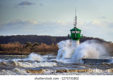 lighthouse during storm in splashing spray in Travemuende, tourist destination on the Baltic Sea in the Luebeck bay, copy space