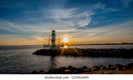 lighthouse of Rostock-Warnemünde in the early morning and an old three master comes in