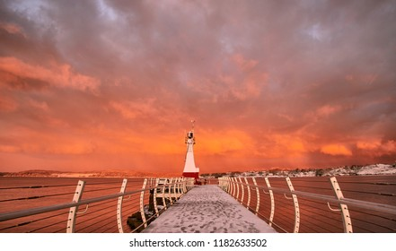 Lighthouse embraced by red clouds