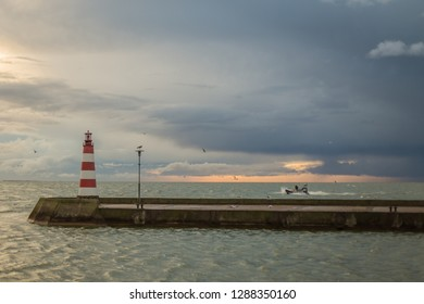 The lighthouse at the entrance to the port of Nida at dawn.