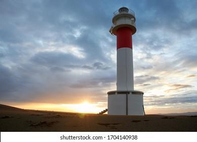 Lighthouse Fangar, in Tarragona, Spain, at sunset
