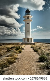 Lighthouse in Formentera island, Spain, the blue sky with white clouds, without people, stones, dry grass