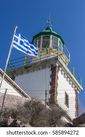 Lighthouse with Greek flag flying.