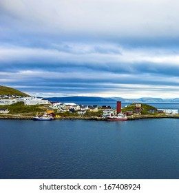 lighthouse and houses of Honningsvag - northern European city in Norway beyond the Arctic Circle in Norwegian fjords.