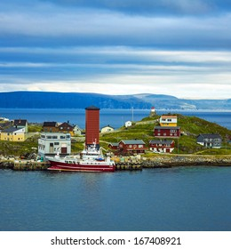 lighthouse and houses of Honningsvag - northernmost European city on the mainland of Norway beyond the Arctic Circle in Norwegian fjords.