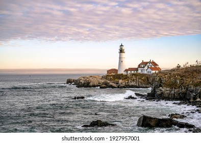 Lighthouse illuminated by the setting sun on a rocky promontory against the backdrop of a cloudy sky on the Atlantic coast in Portland Maine New England showing the ships a safe way to go