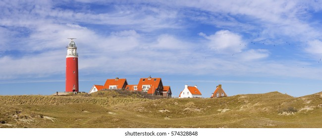 The lighthouse of the island of Texel in The Netherlands on a sunny day. Photographed from across the dunes.