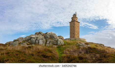 The lighthouse of La Coruna is the oldest in the world and is located in northern Spain on the Atlantic. The Hercules tower stands on a rock. The sky is blue with some clouds.