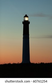 lighthouse lighted at dusk, sein island, brittany, france