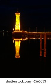 the lighthouse in Lindau at night is reflected in the Bodensee