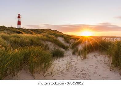 Lighthouse List East at sunset with sunstar, Ellenbogen, Sylt, Schleswig-Holstein, Germany