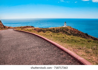Lighthouse located in the north edge of New Zealand, Cape Reinga is seen in the distance with path leading to it.