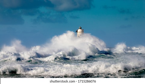 The lighthouse of the Mangiabarche shrouded by the waves of a mistral wind storm
