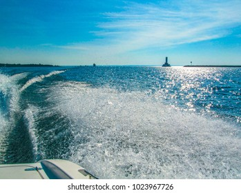 Lighthouse near Mackinac Island, Michigan, USA Horizontal sunny days view from the water surface when the boat moves at high speed and creates a wave and water splashes.