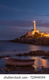 Lighthouse at night with boat in foreground