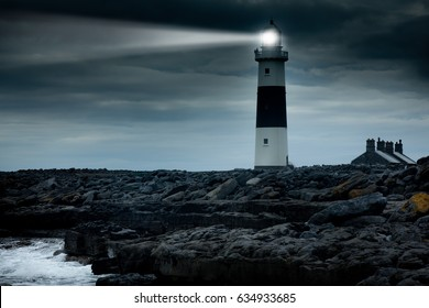 lighthouse at night with spotlight beam. Ireland