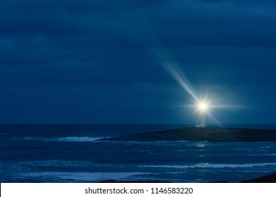 Lighthouse at night under heavy cloud on dark peninsula