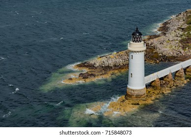 Lighthouse on the Atlantic ocean cliff Scotland with stormy sea and sky with clouds in summer